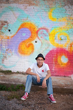 boy sitting in front of a street art painted wall