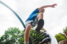 a boy child jumping off playground equipment