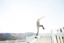 A boy jumping over a fence into the sunlight.