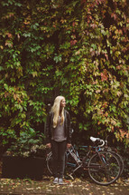 blonde woman standing outdoors next to a bicycle