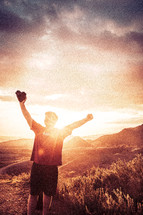 man standing on a mountaintop with raised hands holding a camera