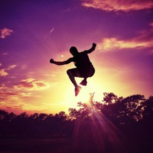 Man jumping in midair at sunset