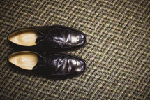 A pair of black dress shoes on the carpet
