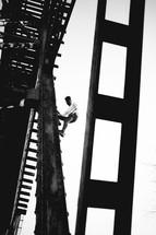 a man climbing a rusty bridge