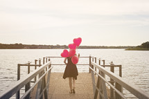 a woman walking on a dock carrying heart shaped helium balloons