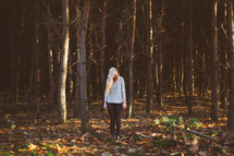 blonde woman standing alone in a forest