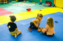 children sitting on mats at daycare