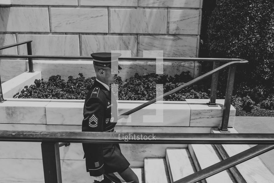 a soldier in uniform walking up steps