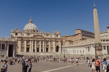 tourists in the colonnade and piazza of st peter's basilica