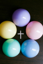 Pastel colored balls surrounding a cross.