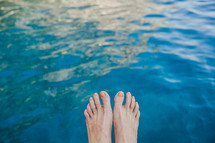 feet hanging over water in Italy