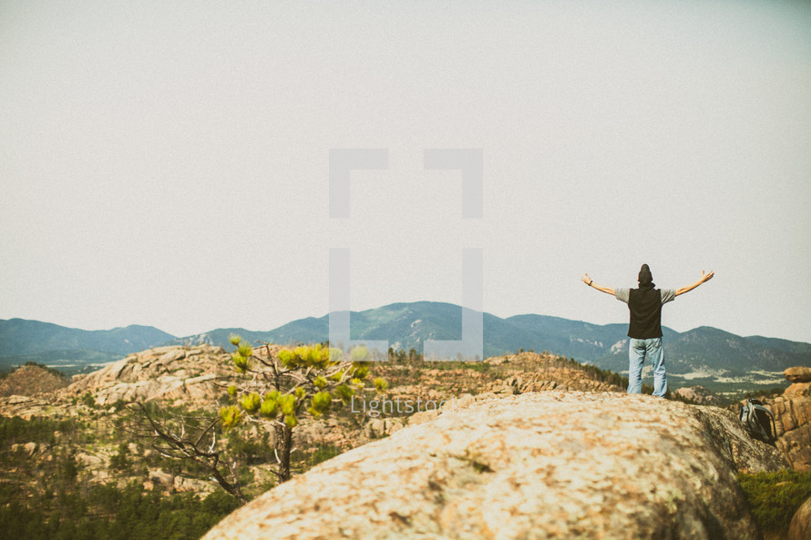 Man standing on a boulder with extended arms.