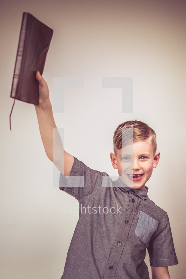 young boy holding up a Bible