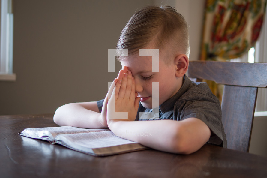 boy child with praying hands over the pages of a Bible