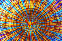 Colorful church stained-glass window with a dove in the center. The Basilica of Our Lady of Peace.