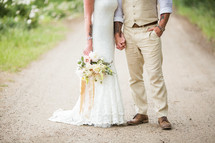 legs of a bride and groom standing on a gravel road
