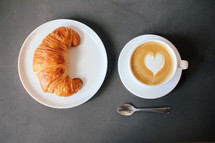 heart shape creamer in a coffee cup and croissant