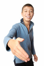 Smiling boy greets with his hand on a white background
