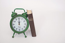 green alarm clock and Bible