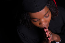 graduate with praying hands