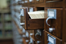 Library card catalog cabinet with an open drawer.
