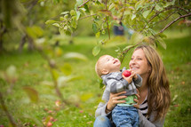 mother and son holding an apple outdoors