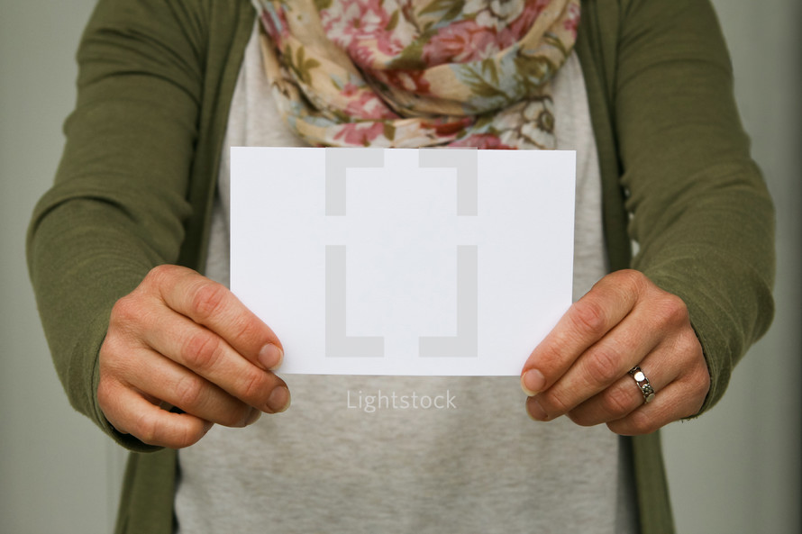 a woman holding up an envelope