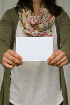 a woman holding up a blank envelope