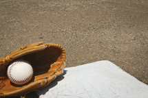 a softball and glove on a base