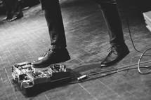 musician adjusting guitar pedals