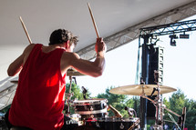 a man playing drums on stage at an outdoor concert