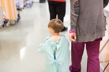 a boy child in a hospital gown walking with a nurse