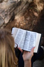 A woman sitting outside reading the Bible.