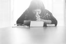 a woman sitting praying over a Bible