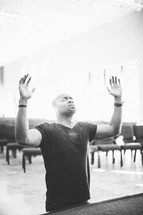 man with his hands raised in praise and worship to God in a church