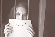 woman hiding behind a smiley face picture, behind bars