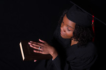 female graduate holding a Bible and praying