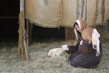 pregnant Mary petting a lamb