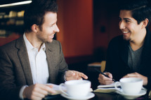 two men smiling and talking over coffee during a Bible study