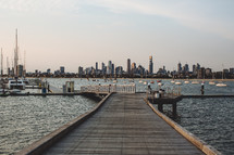 A wooden pier leading into a bay full of anchored sailboats with a city skyline in the background.