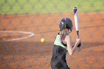 a girl swinging a bat