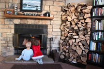 children sitting in front of a fire in a fireplace