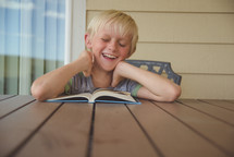 boy child reading a book outdoors