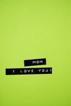 """Mom, I love you,"" on a green background."