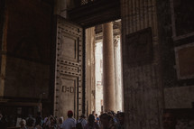 crowds walking through doors of a church in Italy