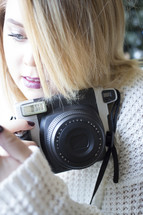 a woman in a sweater holding a camera