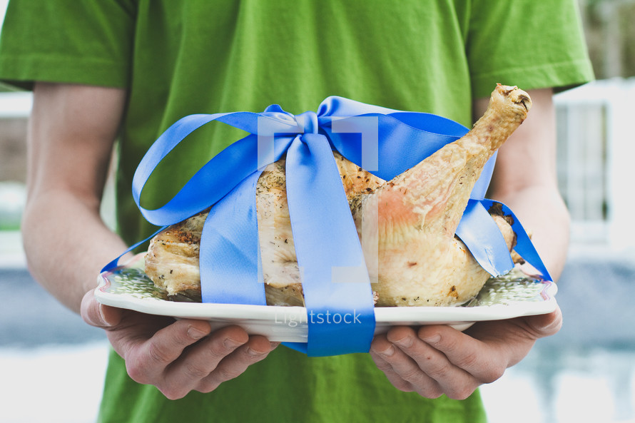 Turkey being served on a platter with a blue bow tied around it.
