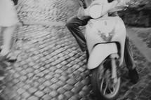 riding a vespa on a narrow street in Italy