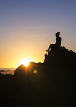 a silhouette of a woman sitting on a rock on a shore at sunset