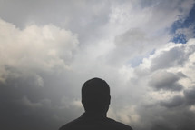 silhouette of a man looking up at clouds